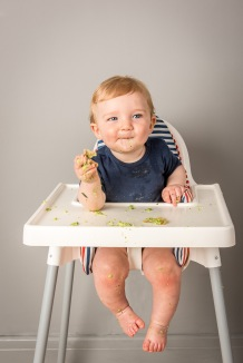 Baby in High Chair eating Veg