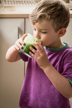 Toddler drinking green smoothie